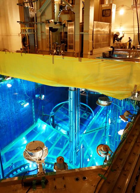 保護ケースに入れられ、クレーンで原子炉容器に運ばれる核燃料=24日午後2時4分、愛媛県伊方町、青山芳久撮影