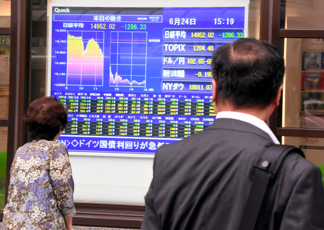 証券会社が店頭に掲げたボードの前で足を止め、株価や為替の変動に見入る人たち=仙台市青葉区