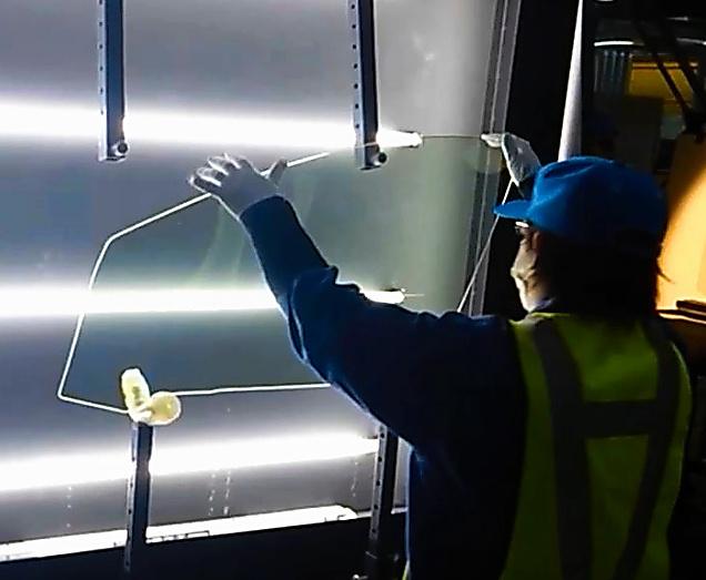 ガラスを検査する従業員=日本板硝子提供