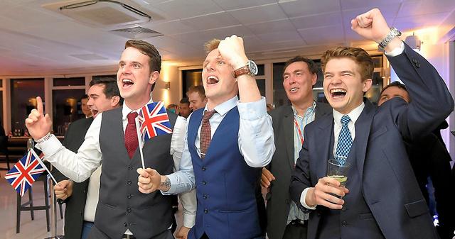 ロンドンで23日、国民投票の開票状況を見て喜ぶEU離脱派の支持者たち=ロイター
