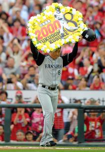 日米通算2千本目となる安打を放ち、ボードを掲げてファンの声援に応える阪神の福留孝介選手=25日午後、広島市のマツダスタジアム、加藤諒撮影
