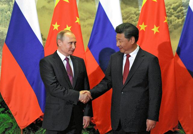 25日、北京での歓迎式典でロシアのプーチン大統領(左)と握手する中国の習近平(シーチンピン)国家主席=ロイター