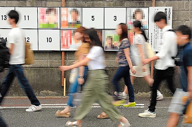 選挙ポスターが貼られた掲示板の前を通学する学生たち=22日、大阪府東大阪市