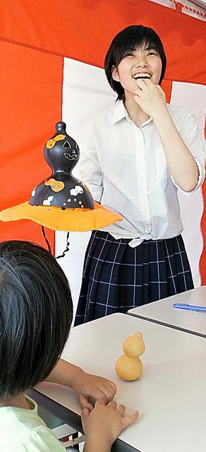 子どもにひょうたんの絵付けを教える大橋さん