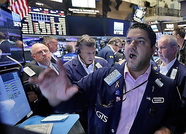 株価急落を受け、ニューヨーク証券取引所のフロアで慌ただしく業務をこなすトレーダー=24日、AP
