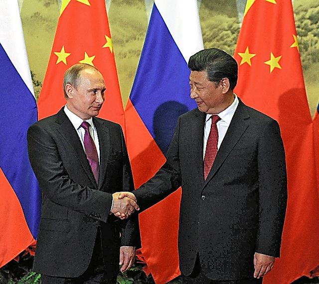 25日、北京での歓迎式典でロシアのプーチン大統領(左)と握手する中国の習近平国家主席=ロイター