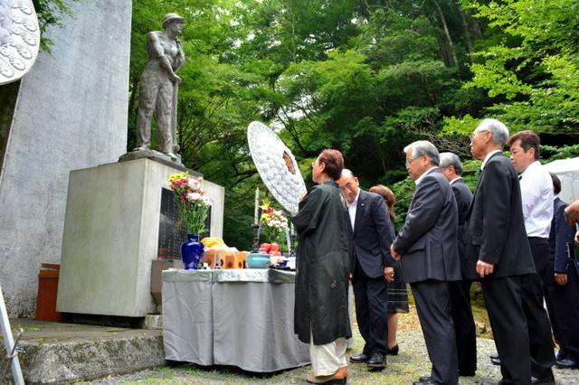 慰霊碑に向かって焼香する参列者たち=26日、西伊豆町大沢里白川