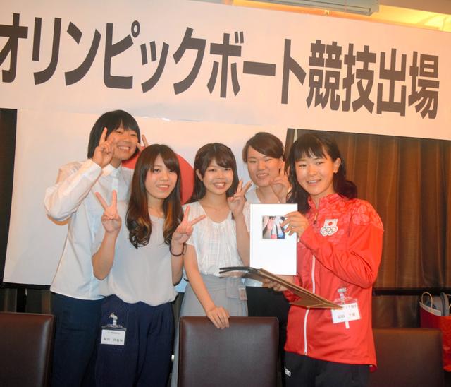 高校の同級生らから贈られた激励のアルバムを手にする冨田千愛選手(右端)=米子市加茂町2丁目