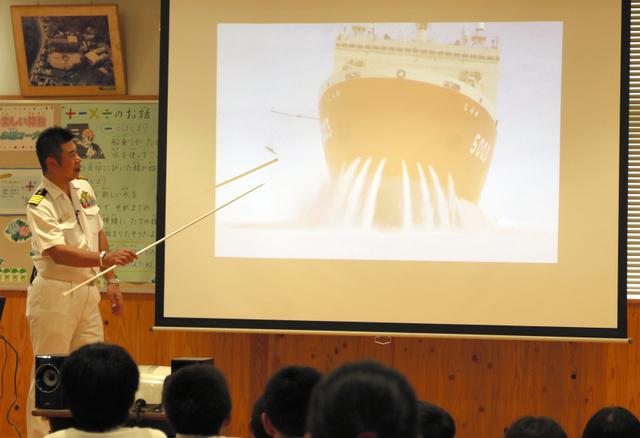 南極観測船「しらせ」が水を放出しながら氷を割って進むラミングの様子を説明する大鋸寿宣艦長=太良町の大浦小学校