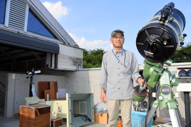 天文台に残った小型望遠鏡と艶島台長。後ろには地震で倒れた中型望遠鏡がある=熊本市南区城南町塚原
