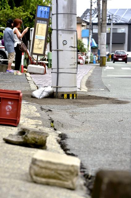熊本地震による液状化で、地中に深く埋まった電柱=26日午前、熊本市南区、福岡亜純撮影