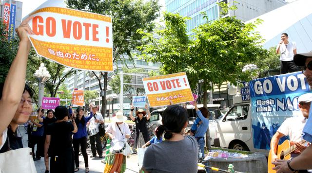 プラカードを掲げ、参院選への投票を呼び掛ける参加者たち=26日午後、名古屋市中区栄、吉本美奈子撮影