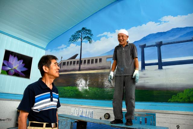 男湯の壁に陸前高田市の「奇跡の一本松」を書き上げた絵師の丸山清人さん(右)と長沼二三六さん=千葉市花見川区