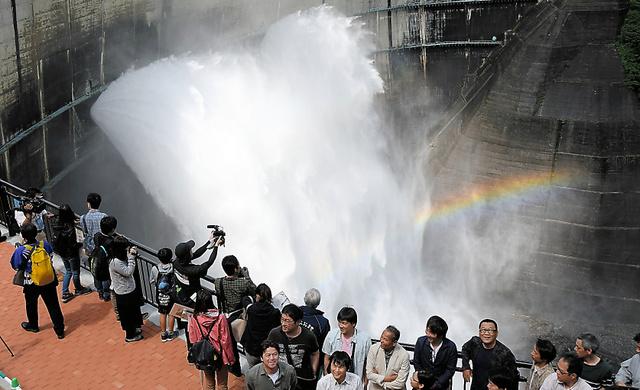 新設された展望テラスから黒部ダムの観光放水と虹を楽しむ観光客ら=26日午前9時44分、富山県立山町、高津守撮影