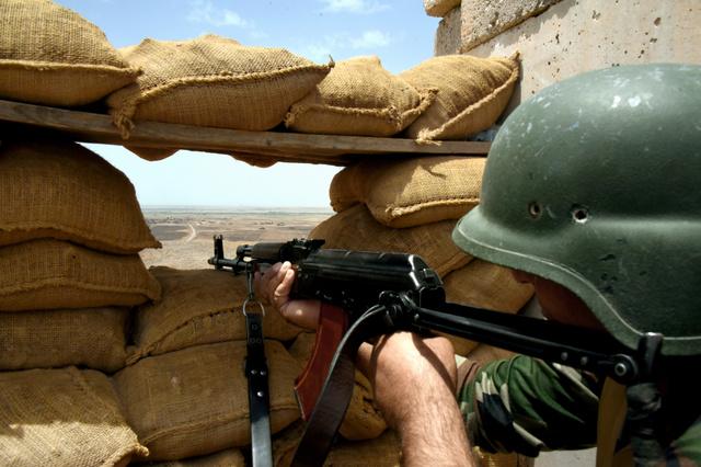 前線拠点で銃を構える隊員。約800メートル先がISに支配された村だ=22日、イラク北部マフムール近郊、渡辺丘撮影