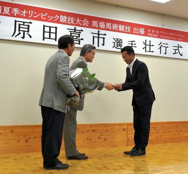 原田喜市さん(右)に太田昇・真庭市長が激励金を手渡した=真庭市久世
