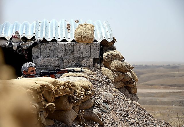 前線拠点で銃を構える隊員。約800メートル先にはISに支配された村がある=22日、マフムール近郊、渡辺淳基撮影