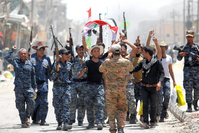 ファルージャ西部で27日、過激派組織「イスラム国」(IS)からの街の奪還を祝う警察官ら=AFP時事