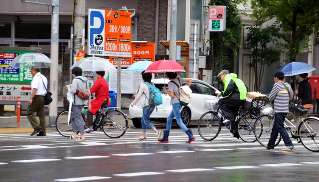 雨の中、道路を横断する自転車と歩行者。傘差し運転も目立つ=28日午前9時33分、大阪市天王寺区、辻村周次郎撮影