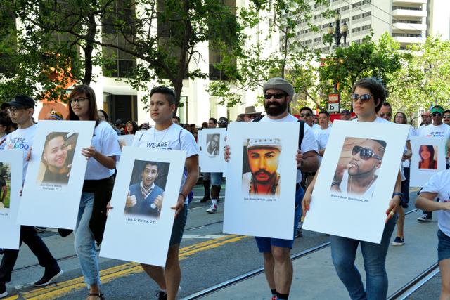 フロリダ州オーランドの銃乱射事件の犠牲者一人一人の写真を掲げて追悼する人たち=サンフランシスコ、宮地ゆう撮影