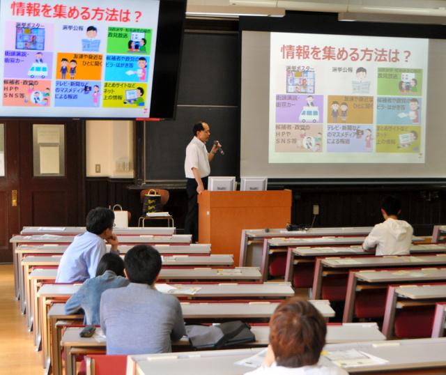 東京都国立市選管が一橋大学で開いた出前授業。風見康裕事務局長は「不在者投票の積極的な利用を」と呼びかけた=1日、東京都国立市