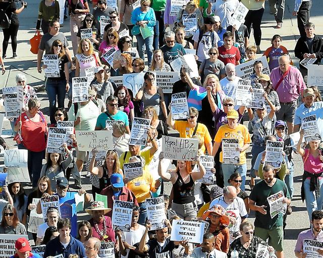 トランスジェンダーの人をめぐる法律に反対し、ノースカロライナ州議事堂に向かうデモ行進の人たち=同州ローリー、中井大助撮影