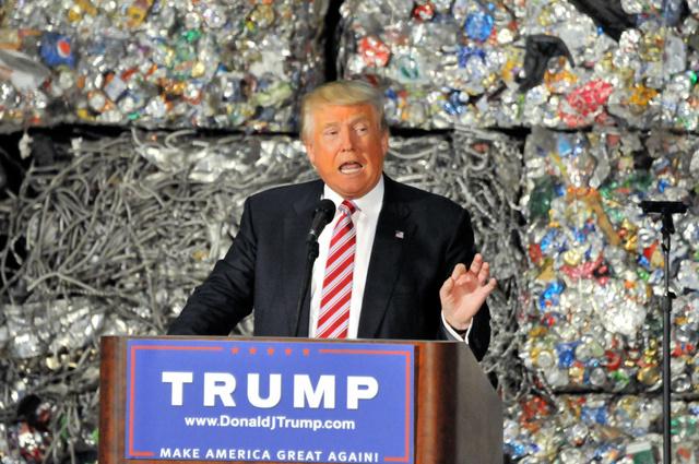 資源再生処理施設で、経済政策について演説する共和党のトランプ氏。背後には、圧縮されたアルミ缶のブロックが積み上がっていた=28日、ペンシルベニア州モネッセン、金成隆一撮影