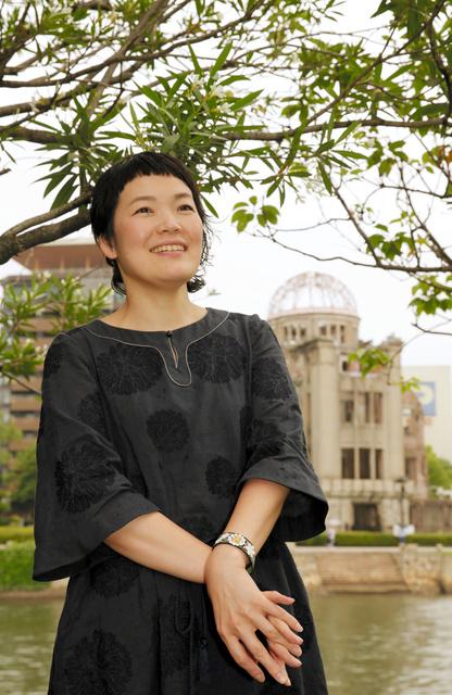 元安川対岸の原爆ドームを背にたたずむ二階堂和美さん=広島市中区、青山芳久撮影