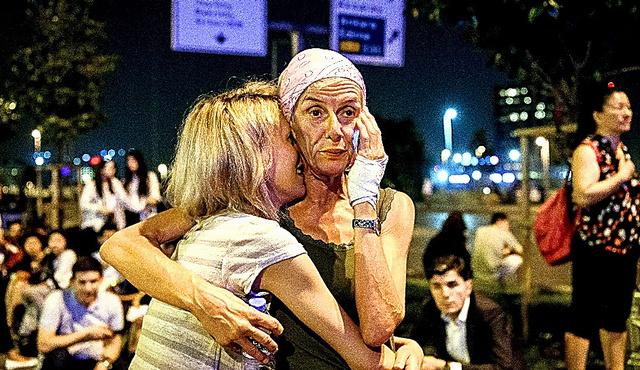 28日、銃撃や爆発のあったイスタンブールの空港から避難し、抱き合う人たち=AFP時事