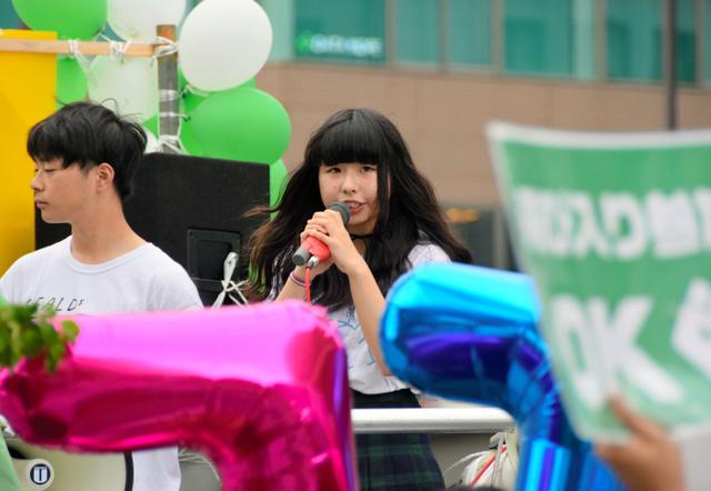風船で飾ったトラックの荷台に立ちデモを先導するせいなさん=仙台市青葉区