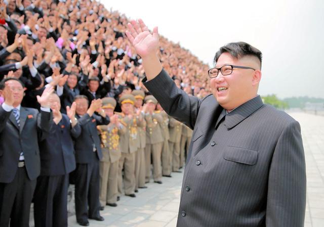 記念撮影場で地対地中長距離戦略弾道ミサイルの試射に寄与した関係者に答礼する金正恩朝鮮労働党委員長。日時、場所は不明。朝鮮中央通信が28日配信した=朝鮮通信