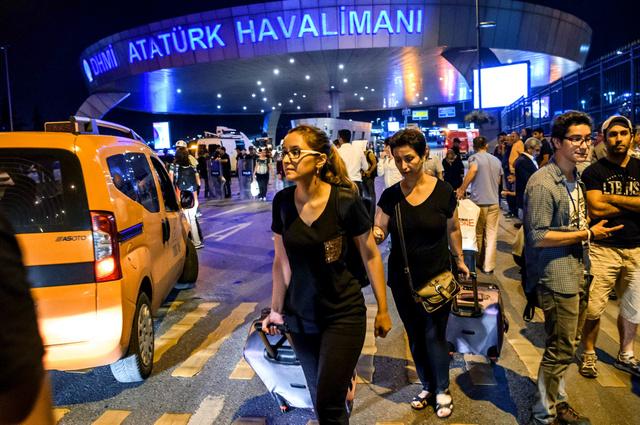 28日、銃撃と爆発があったアタチュルク国際空港から避難する利用客ら=AFP時事