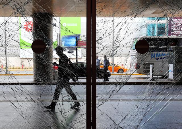 29日、イスタンブールのアタチュルク国際空港のガラスのドアの向こうを歩く男性=ロイター。28日の銃撃や爆発の影響で、ガラスはひび割れていた