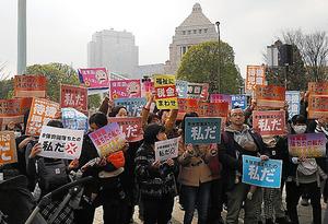 「保育園落ちたの私だ」などの紙を掲げて東京・永田町の国会議事堂前に立つ人たち=3月5日