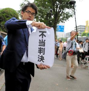 「横浜事件」で国の賠償責任が認められず、「不当判決」の文字を見せる弁護士=30日午後1時13分、東京都千代田区、時津剛撮影