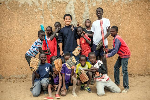 セネガルで野球を教える小川龍馬(中央)と少年たち=Jane Hahn/(C)2016 The New York Times