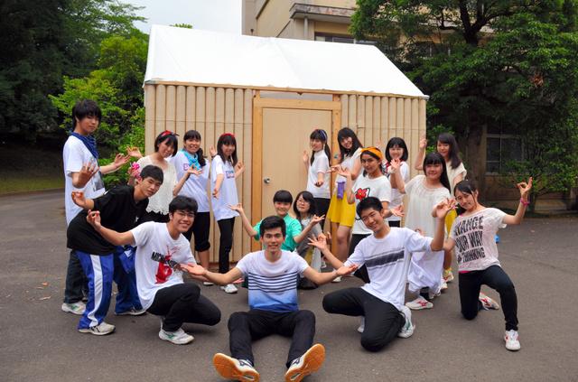 完成した紙管のログハウスの前で、ポーズをとる成田国際高校の生徒ら=成田市加良部3丁目