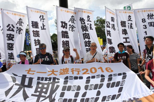 横断幕を持つデモの参加者=1日、香港、益満雄一郎撮影