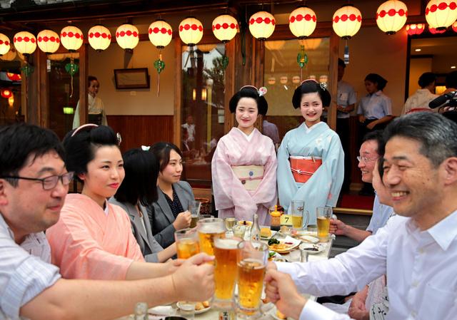 花街・上七軒のビアガーデンがオープンし、浴衣姿の舞妓たちと乾杯する客たち=1日午後、京都市上京区、佐藤慈子撮影