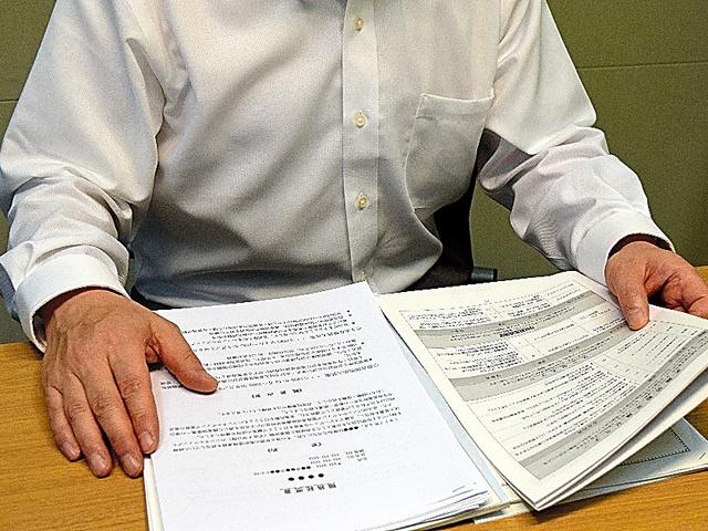 転職活動の書類を読む男性。40社以上に応募したが面接に進めたのはわずかだった=東京都内