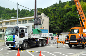 汚染土が入った黒い袋がクレーンでトラックに積まれて大熊町へ向かった=いわき市平赤井の市立赤井中学校