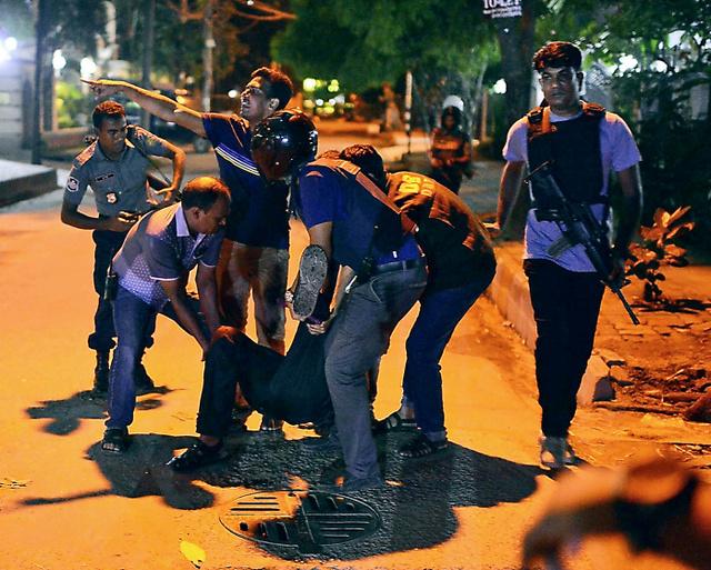 ダッカで1日、レストランが武装グループに襲撃された現場で、負傷者を助ける人たち=AP