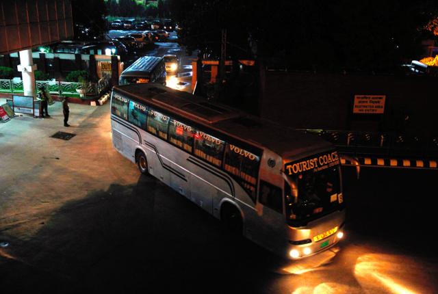 政府専用機でダッカに到着した関係者を乗せて空港を後にするバスの列=3日午後11時12分、関田航撮影