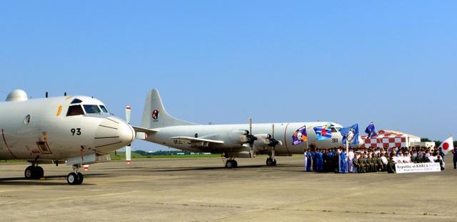 訪日した韓国海軍機P3CK(右)の前で記念撮影する韓国海軍兵士と海上自衛隊員ら。左の機体は海自のP3C=厚木基地