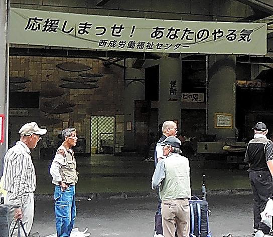 「応援しまっせ! あなたのやる気」という言葉が掲げられた施設に多くの労働者たちが集まっていた=大阪市西成区