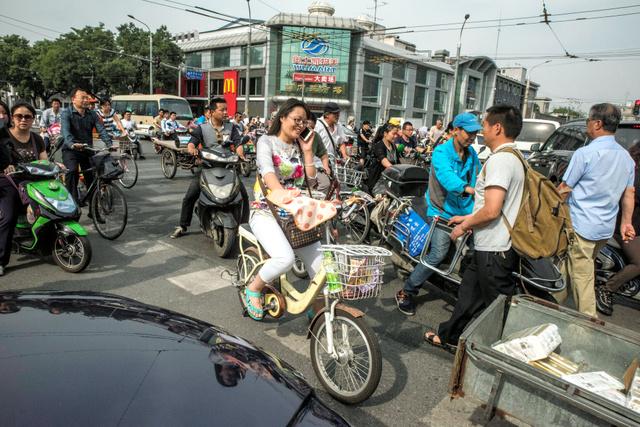 車が行き交う中、北京市内で電動自転車を走らせる女性=Gilles Sabrie/(C)2016 The New York Times。スマートフォンを手に片手運転だ