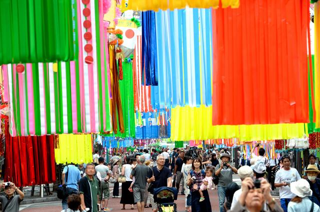 色とりどりの大きな七夕飾りの下を歩く人たち=8日午前、神奈川県平塚市、角野貴之撮影