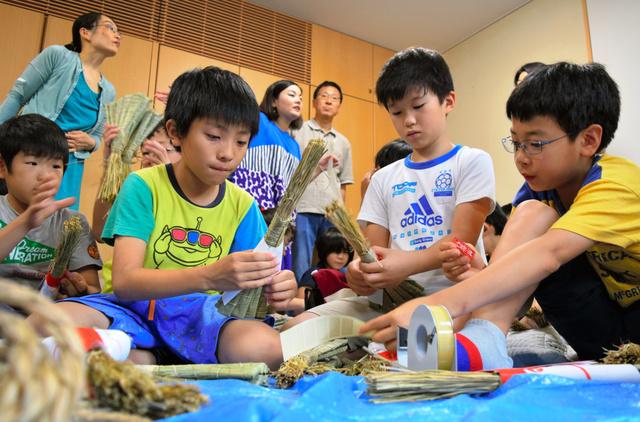 町内の人の指導を受け、厄よけちまきの仕上げ作業をする小学生たち=中京区