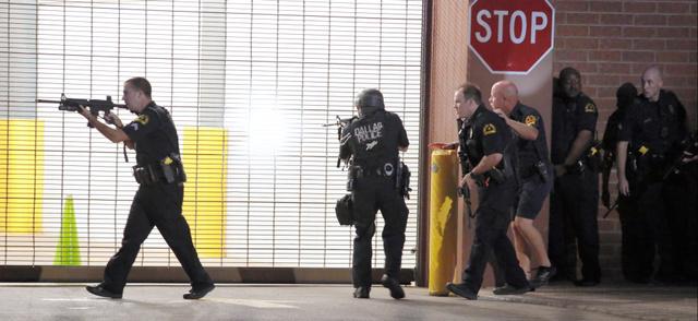 ダラスで7日夜に起きた警官狙撃事件で、応戦するため銃を構える警察官たち。地元紙「ダラス・モーニングニュース」から=AP