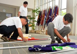 開会式で使う校旗やプラカードを準備する県高野連の関係者。後ろには各校の校旗が並んでいる